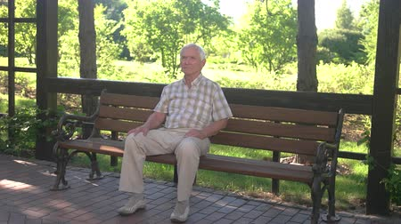 осуществлять : Elderly man sitting on bench. Senior male in the park. Age and wisdom. Quiet day in the park.