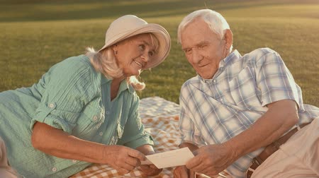 запомнить : Senior couple looking at photograph. Smiling woman looks at man. Lots of good memories. Time is running so fast.