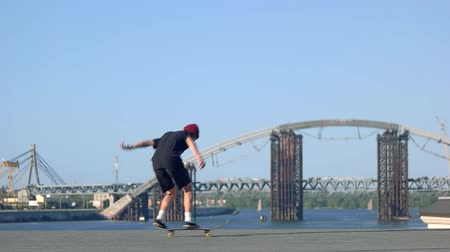 boldness : Trick of skateboarder in slow-mo. Skateboarder on background of bridge. Youth likes extreme. Pop shove it tutorial.