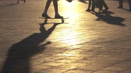 boldness : Skate trick in slow motion. Legs of people on pavement. Master the stunts. Hobby of youngsters.
