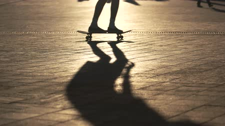 boldness : Legs perform skateboarding trick. Shadow of skater on pavement. Adrenaline for youth. Sportsman is sharpening skills.