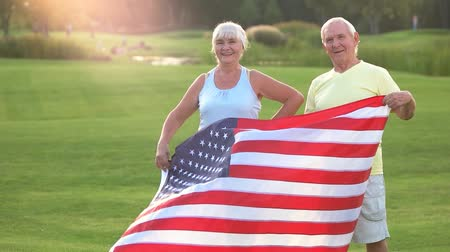 vlastenectví : Senior couple with American flag. Smiling people outdoor. Former champions. Pride of nation.