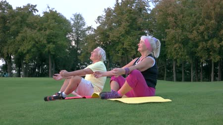 strong granny : Elderly couple doing yoga. People sitting outdoor. Health of body and mind. Find balance inside yourself.