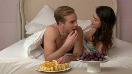 kahvaltı : Couple eating in bed. Plates with fruit in bedroom. Share with me. Romantic breakfast for two. Stok Video