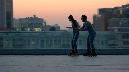 patim : Couple rollerblading in the evening. Man holding woman by waist. Learn to keep the balance. Always by your side. Vídeos