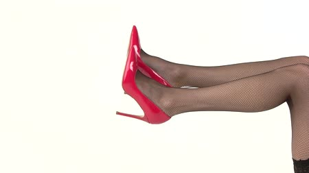 vysoký : Legs in red heels isolated. Fishnet tights and footwear. Look stylish and chic. Designer shoes at best price. Dostupné videozáznamy
