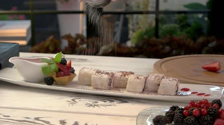 tartlet : Sushi dessert with berries. Chef adding powdered sugar. How top prepare sweet delicacy. Stock Footage
