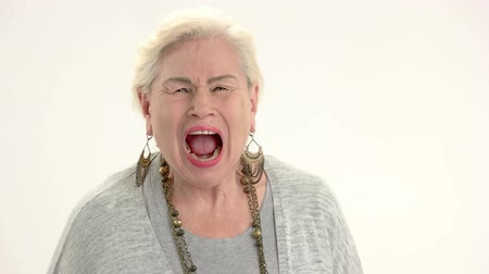 řvát : Woman shouting on white background. Senior lady in pain. Medication side effect.