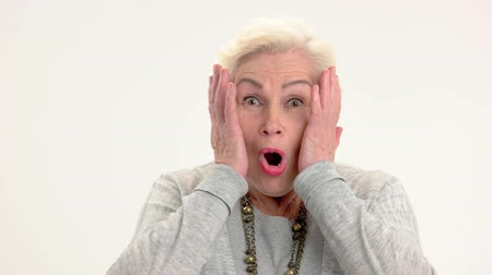осуществлять : Surprised elderly lady isolated. Female with hands on face. See the unbelievable.