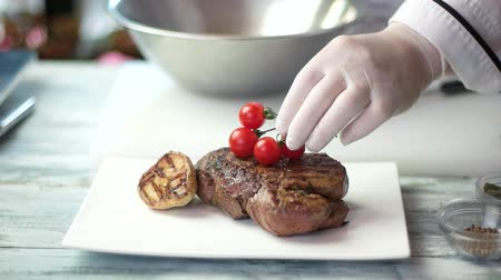 veal recipe : Grilled steak on white plate. Hand holding cherry tomatoes. How to present a dish.