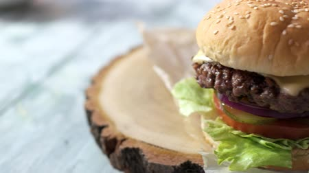 hátrány : Closeup of cheeseburger. Meat and grilled lettuce leaves. Fast food disadvantages. Stock mozgókép