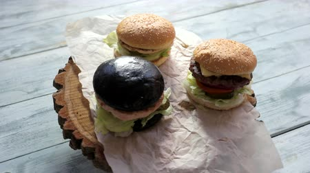 barbecue set : Burgers on wooden board rotating. Dark and light buns. Tastiest hamburgers at special price. Stock Footage