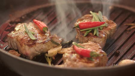 veal recipe : Meat pieces in frying pan. Little chili peppers and rosemary. Invent a recipe of veal. Stock Footage