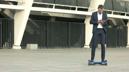 oblek : Businessman on gyroboard. Man holding tablet outdoor. Motion is success.