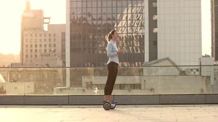 skútr : Woman on city background, slow-mo. Person on hoverboard holding tablet.