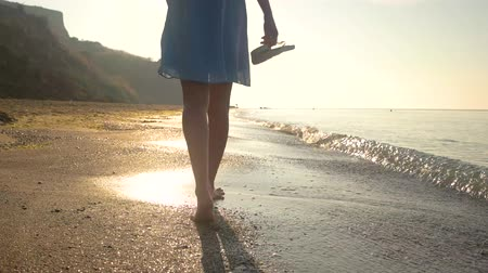 step : Legs of woman walking, seashore. Person carrying flip flops.