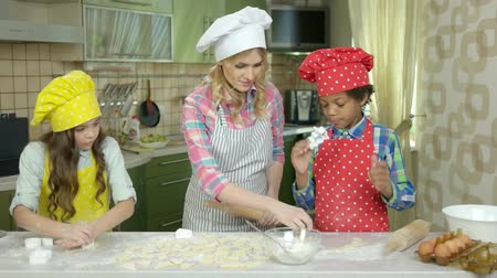 culinária : Smiling woman and kids kitchen. Children make pastry. Stock Footage