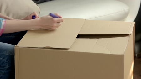posta kutusu : Female hands packing a box. Cardboard box with clothes. Stok Video