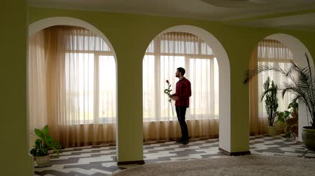 bogaty : Man holding rose near window. Guy with flower standing indoor. Waiting for girlfriend.