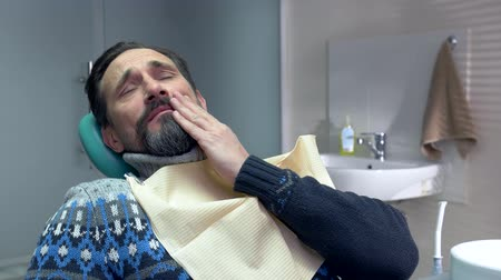 ból zęba : Mature man in dental chair. Adult male having toothache. Get rid of tooth pain. Wideo