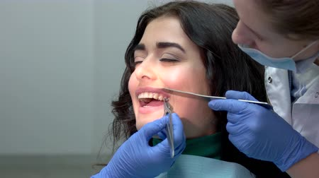 braces : Dentist installing teeth braces. Hands of doctors in gloves. Dental brackets, pros and cons.