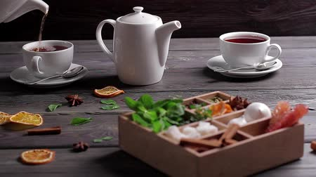 bizet : Tea is pour into the cup. Wooden box with mixed spices, cups and teapot.