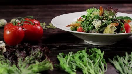 dorblu : Salad with shrimps and ingredients on a wooden background. Salad pour of balsamic sauce. Stock Footage