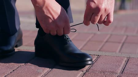 politikacı : man tying shoelaces on leather shoes