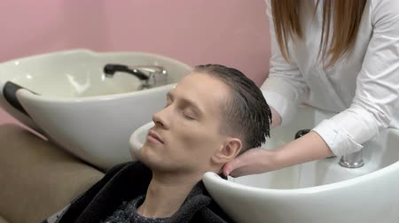 mycie rąk : Man getting his head washed. Caucasian guy in hair salon.
