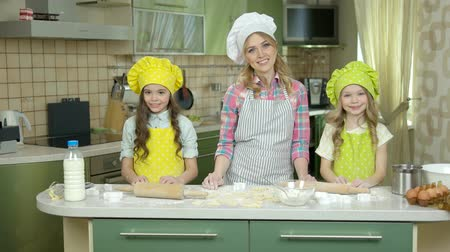 turta : Happy female chef and kids. Smiling people in the kitchen. Food and cooking shows.