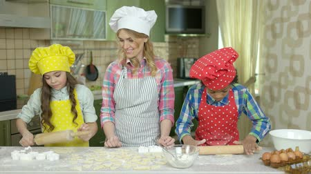 culinary : Happy woman and kids, kitchen. Children working with dough.