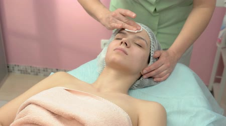 toner : Cosmetician wiping skin. Young woman in wellness clinic.