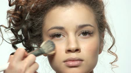tarz : Hand with brush applying makeup. Face of pretty young model.