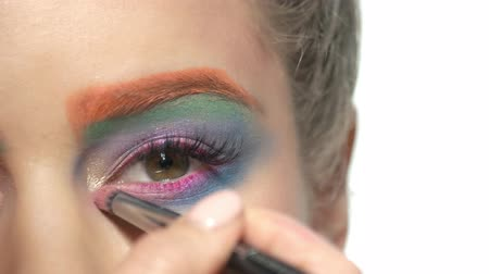 paleta : Eyeshadow applying close up. Eye of young woman, makeup.