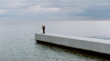 супруг : Bride and groom lovingly hugging on the seaside.