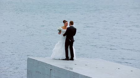 fidelity : Bride and groom cute kissing and cuddling on the background of the sea.
