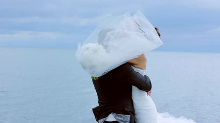 fidelity : Groom gently whirl the bride on a background of the sea. Stock Footage