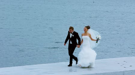fidelity : Bride and groom running along the waterfront on the background of the ocean.