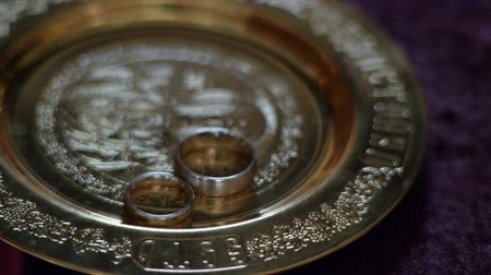fiancee : Wedding rings on a saucer in the church. Wedding ceremony. Rings of the bride and groom. Stock Footage