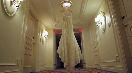 żyrandol : The brides dress hangs on a hanger in the hall. Wedding preparations. Wedding day. Nice dress.