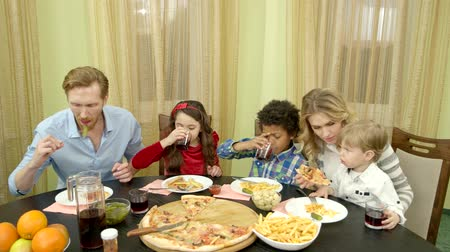 жарить : Family having dinner indoors. People drinking and eating.