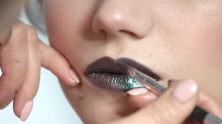 dokonalost : Brush applying black lipstick. Lips of young model, makeup.