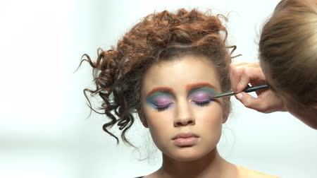 paleta : Makeup artist applying eyeshadow isolated. Young model on white background.