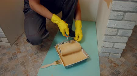 construtor : Builder ready to paint the walls. House painter rolling a roller into the paint. Stock Footage