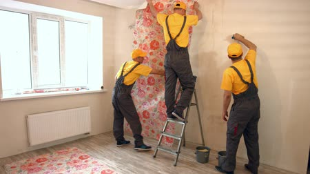 laminált : Specialists wallpapering in the house. Brigade of craftsmen making renovation.
