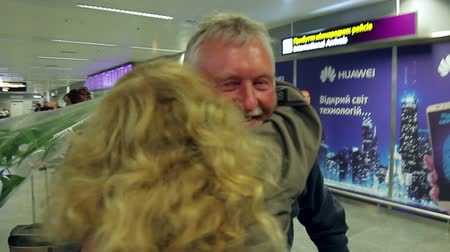 emocional : Wife meets her husband at the airport with flowers. Hugs of two loving people. Vídeos