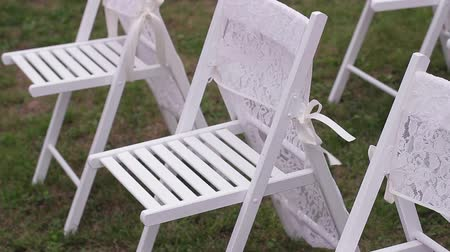 assentos : Beautiful white chairs with a light cloth for the wedding ceremony. Wedding day. Stock Footage