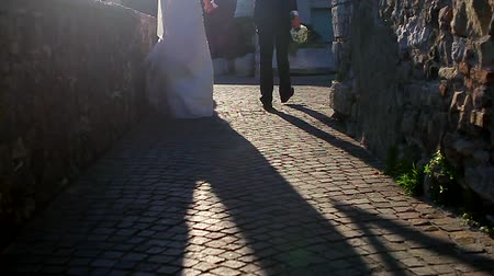 paving : Bride and groom are go on the old street and holding hands.