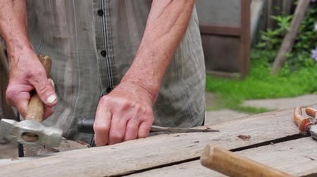 ручная работа : Old man takes out the nails. Old mans hands working. Стоковые видеозаписи