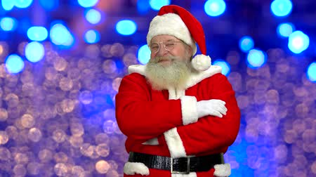 gelenek : Santa Claus, blurred lights background. Happy Santa, folded arms. New Year resolutions. Stok Video